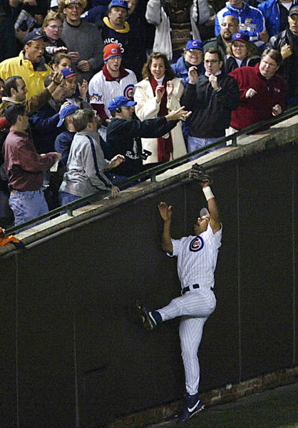 Fans interfere with outfielder Moises Alou on a ball hit by Luis Castillo of the Florida Marlins in the eighth inning during Game 6 of the National League Championship Series October 14, 2003 at Wrigley Field in Chicago, Illinois.