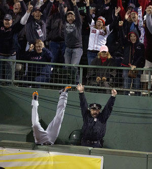 Fans and Boston Police officer Steve Horgan celebrate as Detroit Tigers' Torii Hunter falls over the right field fence into the bullpen trying to catch a grand slam hit by David Ortiz during Game 2.