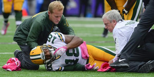 Green Bay Packers wide receiver Randall Cobb is attended to by training staff after suffering an injury against the Baltimore Ravens.