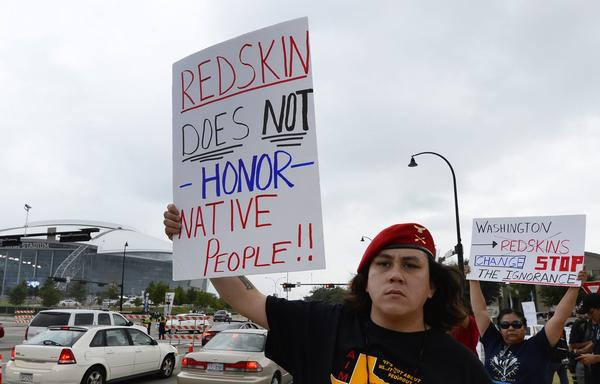 Demonstrators hold up signs in protest of the Washington Redskins name outside the AT&T Stadium in Arlington, Texas.