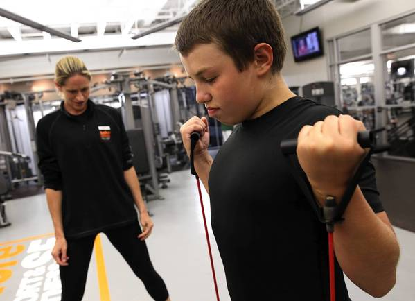 Personal trainer Carey Scheuler works with 13-year-old client Leonardo Serafini. More parents are hiring trainers to work with their children as sedentary play options continue to proliferate.