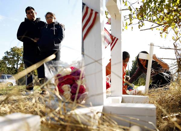 Omar Cid and Itzel Carrillo, standing left, visit a memorial for the Aurora crash that killed three people.