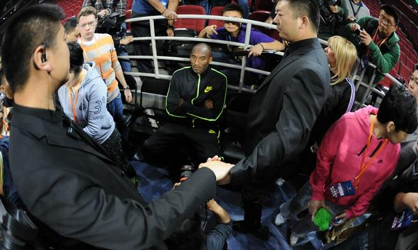 Lakers star Kobe Bryant sits inside a ring of security guards while doing an interview prior to practice at the 2013 Global Games in Beijing on Monday.