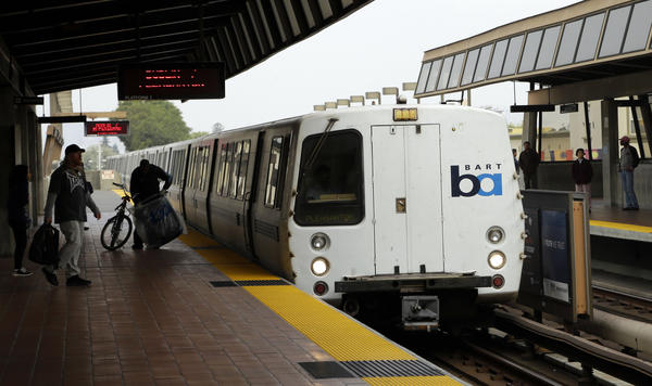 Bay Area Rapid Transit travelers wait to board an arriving train in Oakland. A regional transit strike seemed likely late Monday as the clock ticked toward an 11:59 p.m. cutoff of negotiations.