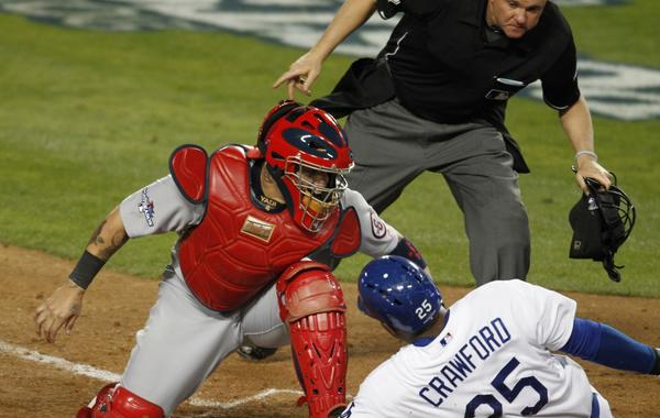 Dodgers left fielder Carl Crawford, right, slides under the tag of Cardinals catcher Yadier Molina to score during the eighth inning of the Dodgers' 3-0 win in Game 3 of the NLCS on Monday.