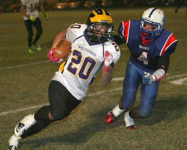 Herreid-Selby Area's Austin Iverson, left, tries to outrun Warner's Clay Rozell, right, during Saturday night's Class 9A semifinal game in Warner. photo by john davis taken 11/3/2012