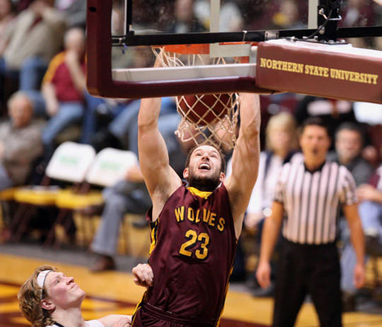 Northern State University's Trent Zomer dunks the ball as Augustana College's Daniel Jansen, lower left, looks on during the first half of Saturday's game at Wachs Arena. photo by john davis taken 2/9/2013