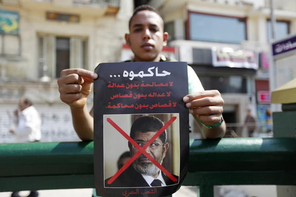 A man carries a poster of ousted Egyptian President Mohamed Mursi, calling for his trial as people gathered to celebrate the anniversary of an attack on Israeli forces during the 1973 war, in Cairo October 6, 2013.