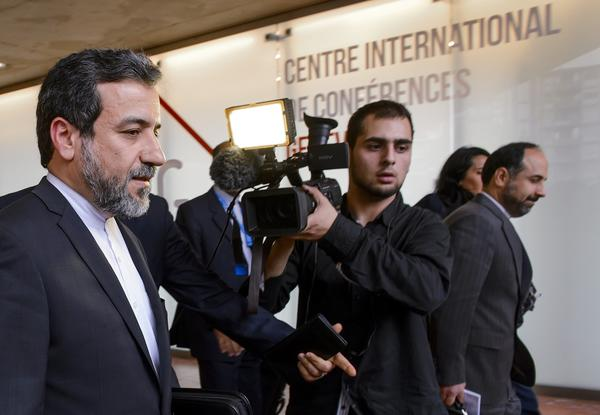 Iran's deputy foreign minister, Abbas Araghchi, left, leaves the media center after the start of two days of closed-door nuclear talks on Tuesday at the United Nations offices in Geneva.