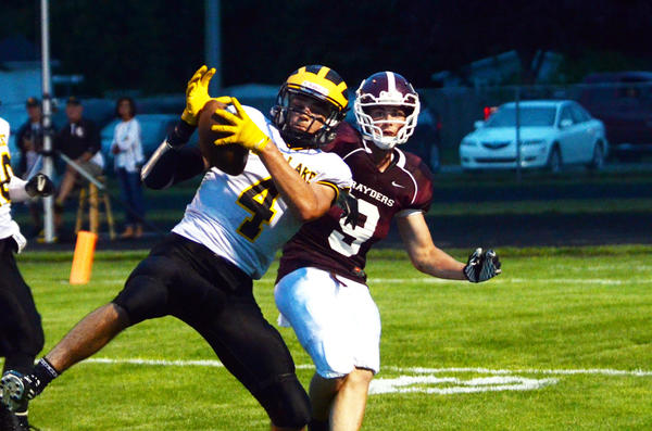 Maple City Glen Lake senior Thomas Waning (4) hauls in a pass in front of Charlevoix junior Nate Moon (right) during a non-league contest earlier this season. Next year, the Rayders and Lakers will play in the same football conference.