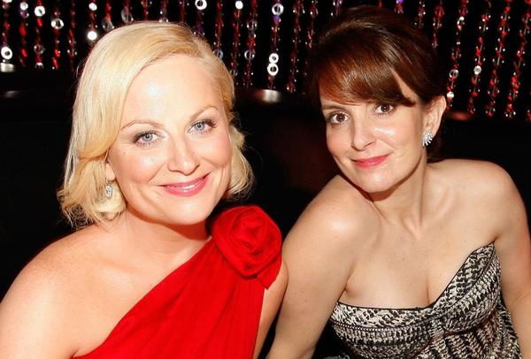 Amy Poehler, left, and Tina Fey will return as hosts for the Golden Globes for the next two years.