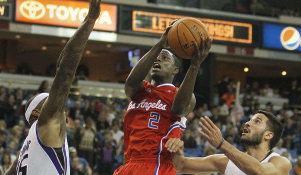 Clippers guard Darren Collison drives to the basket between Sacramento's DeMarcus Cousins, left, and Greivis Vasquez on Monday night.