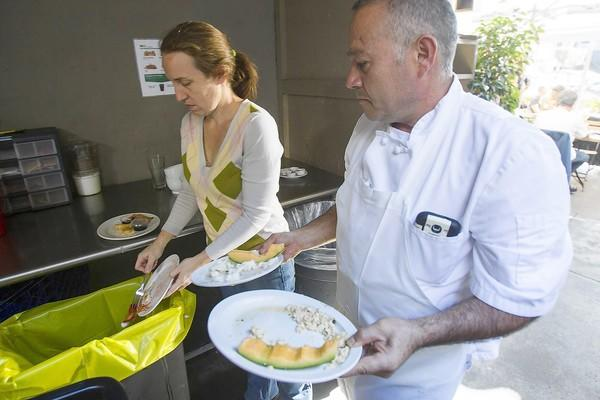 Tami Spain, the general manager, and Simon Virgen, the kitchen manager at Zinc Cafe, separate food waste into a colored plastic bag on Tuesday.
