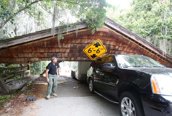 Demolition expert Mickey Grosman looks at truck and trailer stuck under the covered bridge. The old covered bridge in Maitland was knocked down on October 14, 2013 by a driver and trailer that was too tall for the six foot six inches of clearance.