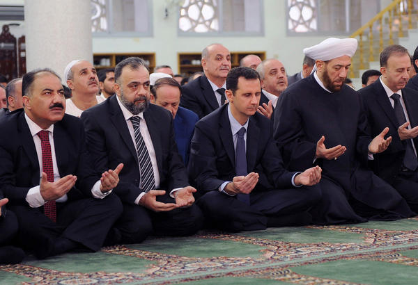 Syrian President Bashar Assad, third from left, attends a prayer service in Damascus marking the Eid al-Adha holiday.