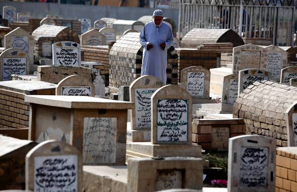 An Iraqi visits a relative's grave in Baghdad for the Eid al-Adha holiday. A new study estimates that nearly half a million Iraqis died as a result of the Iraq war.