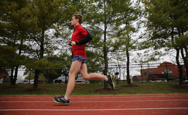 Johnny Crain, a leading runner on Division III powerhouse cross-country North Central team warms, up on the track before heading to the streets and parks of Naperville.