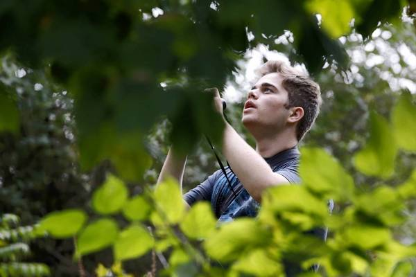Aaron Gyllenhaal, 16, of Oak Park, looks for birds Sunday at the Magic Hedge, a popular spot for viewing migrating birds near Montrose Harbor.