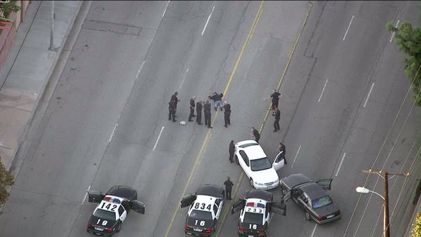 A driver is surrounded by officers after a high-speed car chase ended at the LAPD Mission Station.