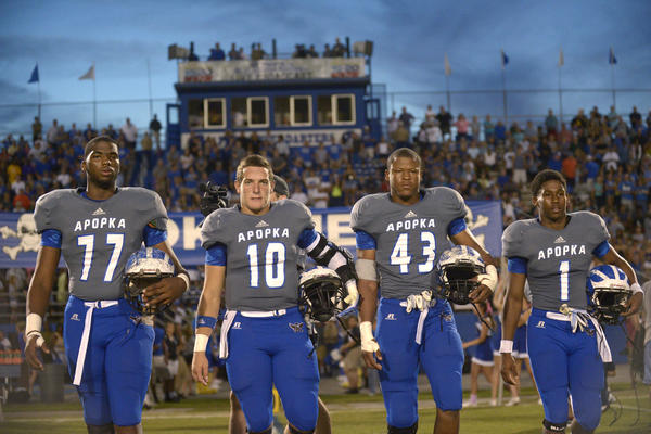 Apopka captains Martez Ivey (77), Chandler Cox (10), Robert Greathouse (43) and Robert Thomas (1) walk to the middle of the field for the coin toss before the start of a high school football game against West Orange.