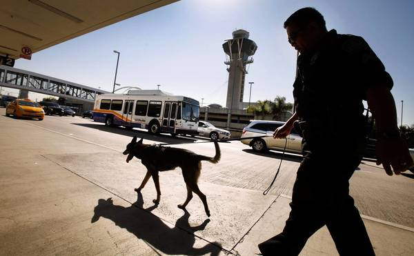 An L.A. Airport Police officer and police dog walk through Terminal 2 on Tuesday morning. Recently, three dry-ice bombs were found.