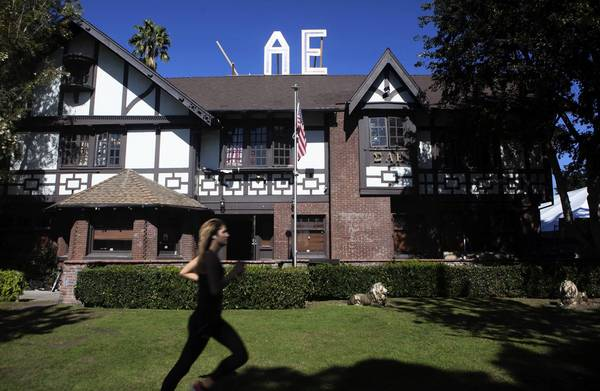 A USC student runs in front of the Sigma Alpha Epsilon house on Greek Row. The fraternity has been put on probation after a student from another college fell from a table during a party last Thursday and was taken to the hospital.