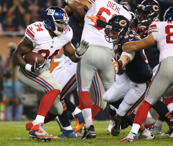 New York Giants running back Brandon Jacobs tries to elude Bears defensive end Shea McClellin.