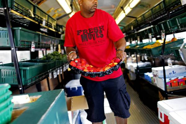 "A ""Fresh Moves"" bus is restocked before heading to the Lawndale neighborhood in July 2012. A month earlier, Mayor Rahm Emanuel had touted the mobile produce markets."