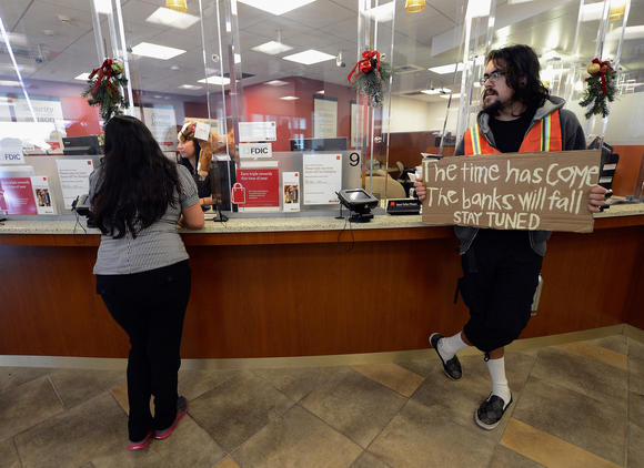 A protestor holds a sign as a bank customers speaks to a bank teller during a demonstration.