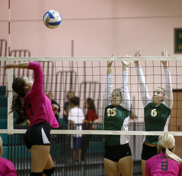 Aberdeen Roncalli's Rachel Kokales (15) and Brooke Olson (6) defend the net as Mobridge-Pollock's Ellie Rabenberg, far left, reaches to hit the ball during Tuesday night's match at the Roncalli High School gym. At right in the foreground for Mobridge-Pollock is Kylee Wagner. American News Photo by John Davis