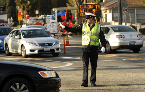 A Los Angeles Department of Transportation traffic officer directs traffic at the intersection of Coldwater Canyon Avenue and Ventura Boulevard in Studio City.