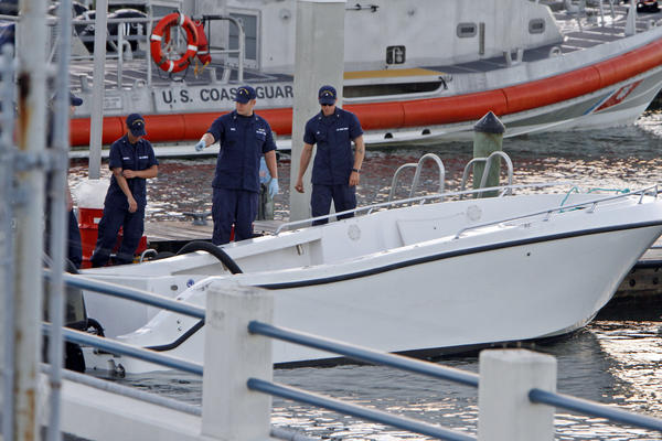 U.S Coast Guard personnel inspect a vessel pulled into shore after it capsized near Miami. At least four women died and 11 people were rescued.