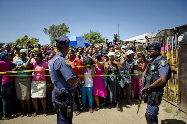 South African police stand guard as residents of Diepsloot township gather near a communal toilet where the bodies of two toddlers were found.