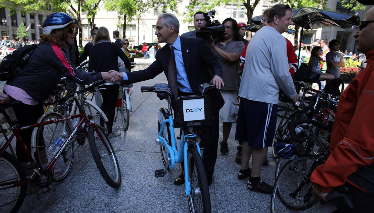 Mayor Rahm Emanuel walks his Divvy bike back after a brief ride at the annual Bike to Work Rally at Daley Plaza on June 14, 2013.