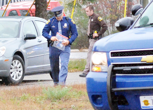 A Michigan State Police trooper carries a bag containing what appears to be the plastic bottle that caused an explosion sound outside the Challenge Mountain Resale Shop around noon Wednesday.