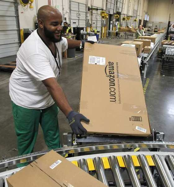 Leacroft Green carries a package to the correct shipping area at an Amazon.com fulfillment center in Goodyear, Ariz. Amazon has just opened two similar facilities in Northern California.