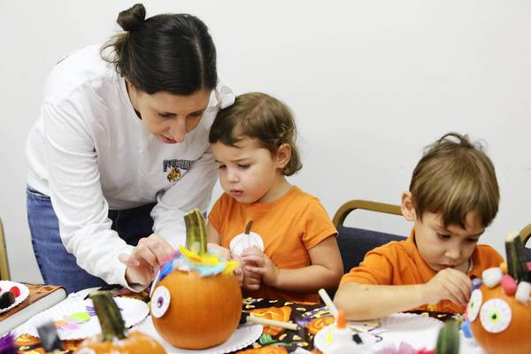 Julie Brewster helps her children, Becca, 2, and Andrew, 3, decorate pumpkins during a Halloween pumpkin decorating workshop at W.T. Bland Library in Mount Dora.