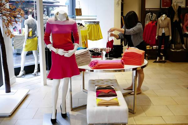 An employee at a Banana Republic store in Los Angeles last week. A national survey of consumers finds that holiday shoppers plan to spend less on gifts for family members this year.