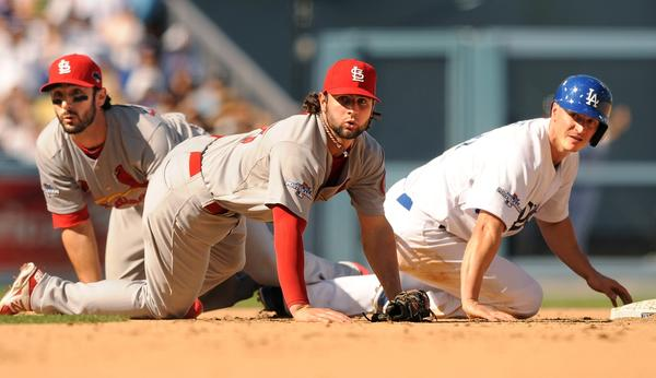 Dodgers second baseman Mark Ellis, right, Cardinals shortstop Pete Kozma, center, and Cardinals second baseman Matt Carpenter look toward first to see that a double play was completed in the third inning of Game 5.