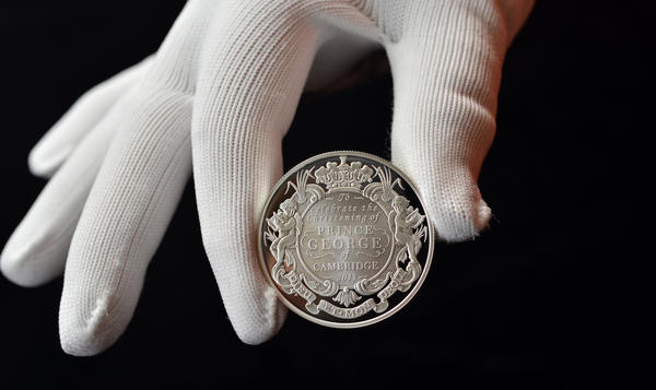 In this undated photo released Tuesday, Oct. 8, 2013, by Solent for the British Royal Mint, a 5 pound (with a face value of $8) silver coin produced to commemorate the upcoming christening of Prince George of Cambridge is displayed.