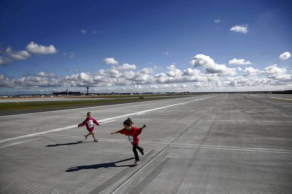 Amelia Skurla and Maya Baum, both 4, play on O'Hare's new runway last month during an event sponsored by the city's Department of Aviation. The runway will open Thursday.