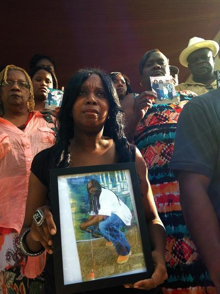 Family members of Tyrone West attend a rally, protesting his death at the hands of police.