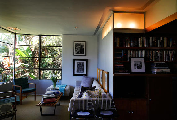 The curving lines of the window are just the first of William Kesling's Streamline Moderne elements in Jay Huguley's house. Huguley chose not to hang curtains, favoring garden views and light over privacy. Note the built-in light box above the bookcase.