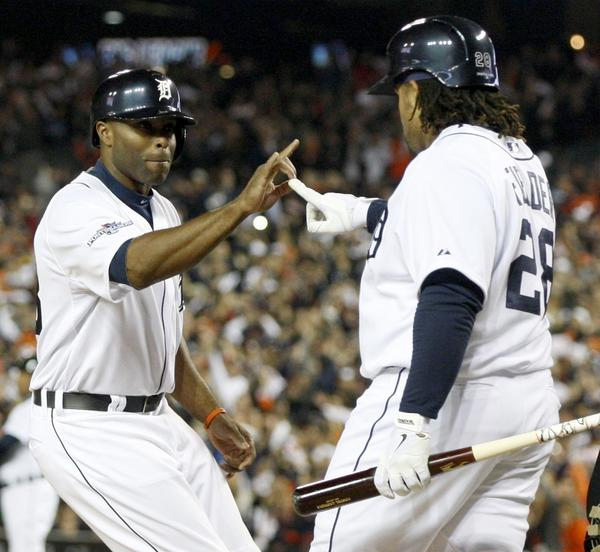 Tigers' Prince Fielder congratulates Torii Hunter, who scores on a base hit by Miguel Cabrera during the second inning.