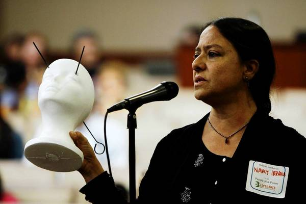 Nancy Halpern Ibrahim, executive director of Esperanza Community Housing Corp., speaks during the town hall meeting. She holds a foam head depicting some of the systems residents are experiencing, such as headaches and nosebleeds.