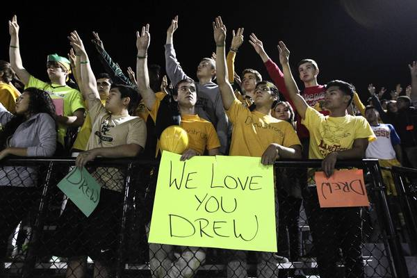 The Lane Tech community honors injured Senior Drew Williams by holding up three fingers during the game against Foreman at Lane Tech High School in Chicago on Oct. 11.
