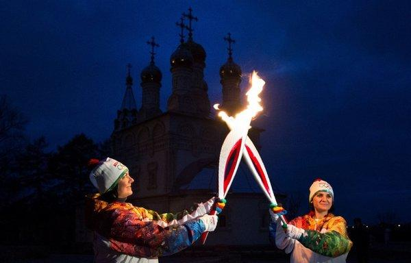 Torchbearers Nataliya Golovina, left, and Olga Puchkova pass the Olympic flame during the Sochi 2014 Winter Olympic torch relay in Ryazan, Russia.