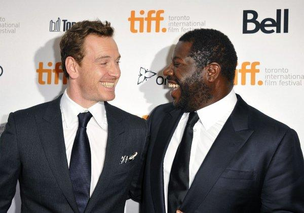 "Michael Fassbender is all smiles at the Toronto Film Festival with ""12 Years a Slave"" director Steve McQueen."
