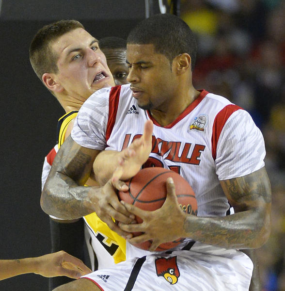 Chane Behanan of the Louisville Cardinals and Mitch McGary of the Michigan Wolverines battle for the ball in the first half of the NCAA Tournament final at the Georgia Dome last April.