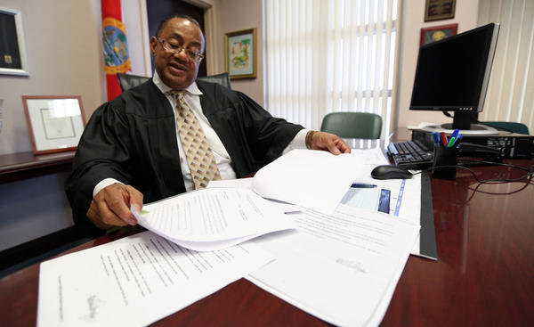 Chief Judge Belvin Perry, Jr. shows some of the forged court orders that led to the erroneous release of two convicted murderers on Thursday, October 17, 2013.